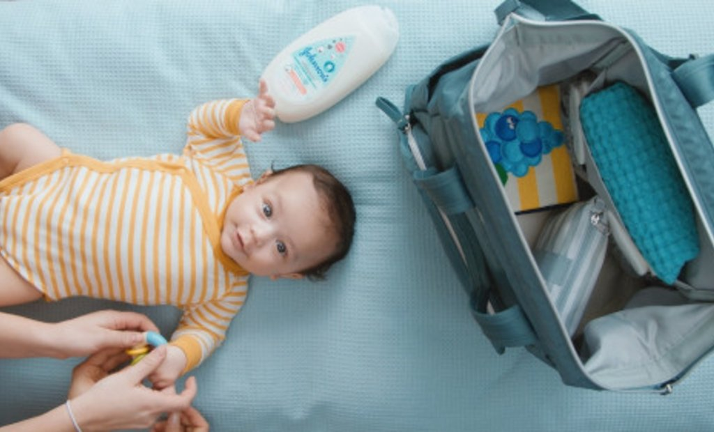 child laying on bed beside travel bag