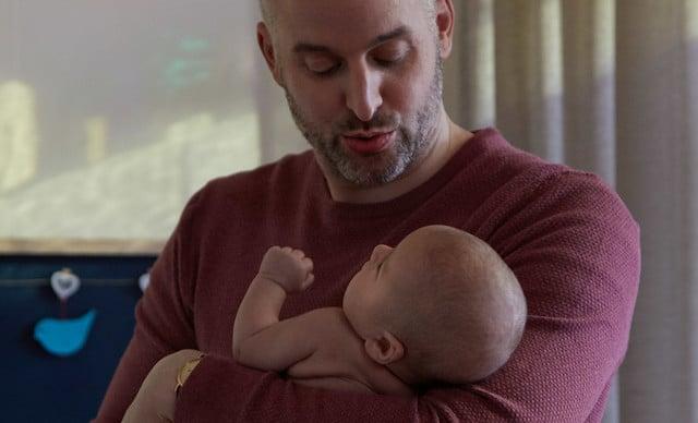 dad putting newborn to sleep