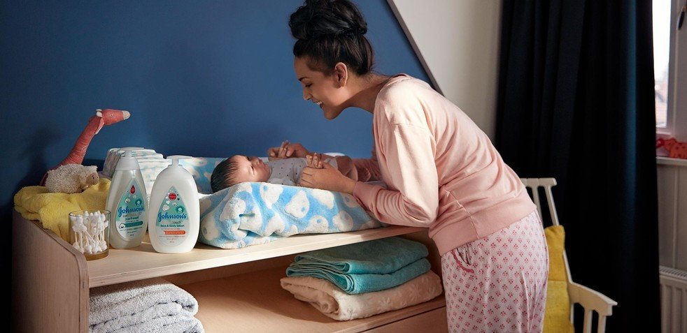 Mother and baby in nursery with Johnson's® baby products