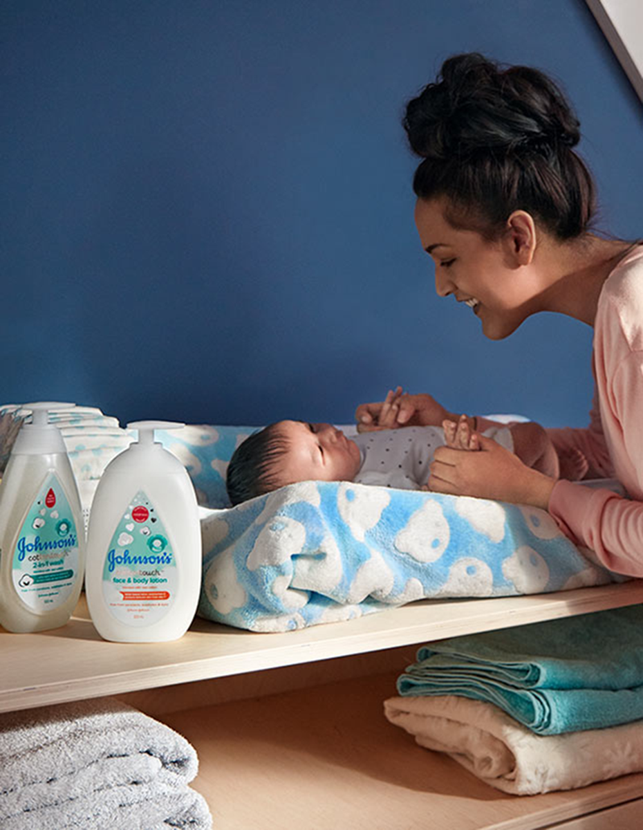 Mother with her baby using Johnson's® CottonTouch™ newborn baby products